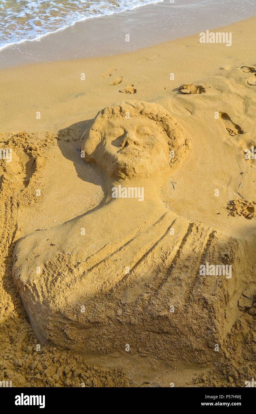 Sand sculpture in the form of an antique statue on the beach. - Stock Image