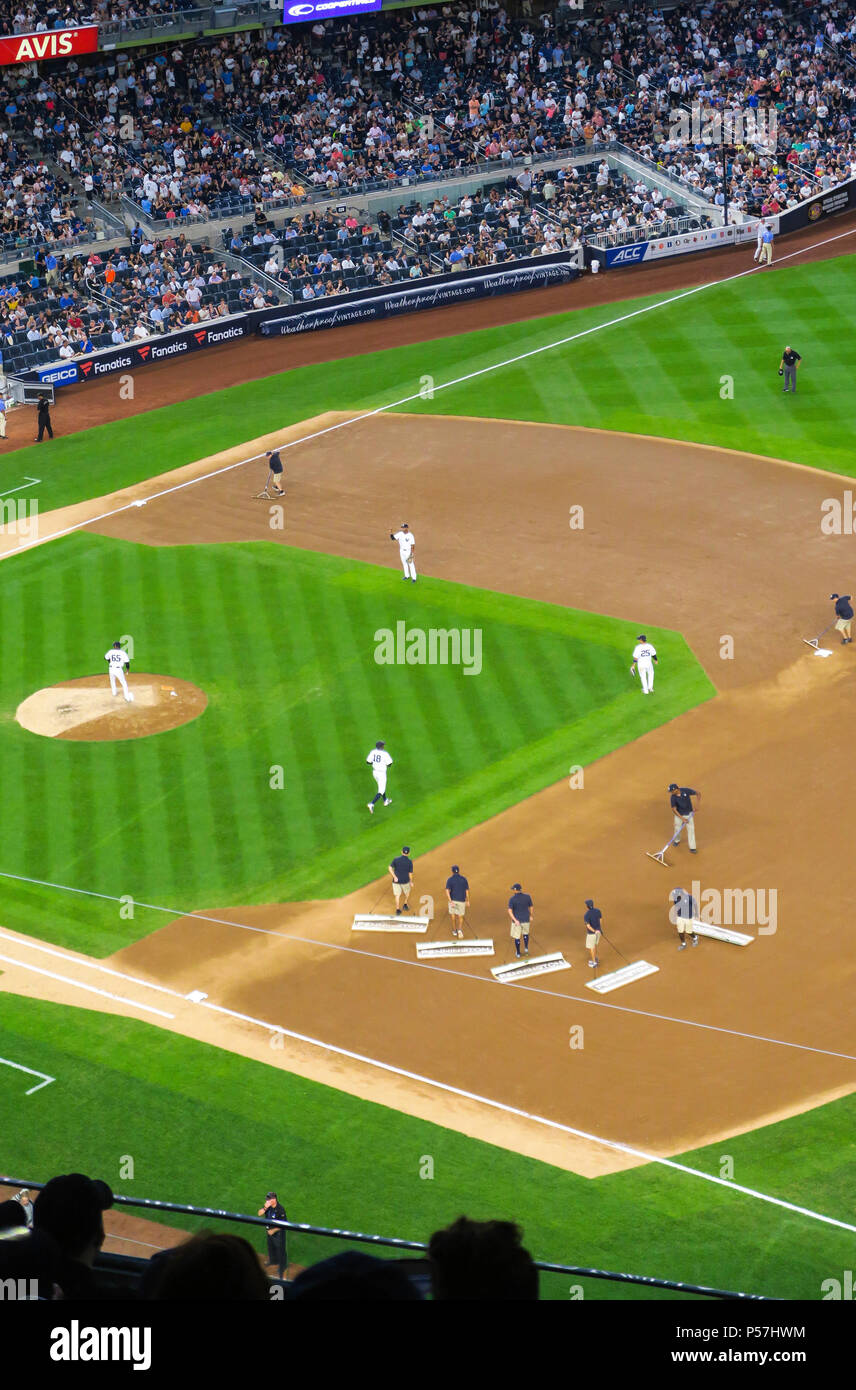 The grounds crew groom the infield dirt between innings during a night game at Yankee Stadium, the Bronx, NYC, USA - Stock Image