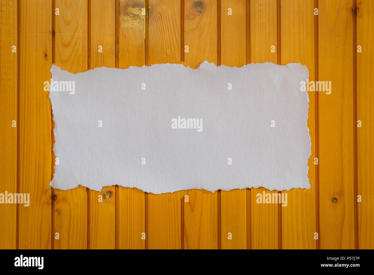White sheet of paper on a wood panelled background for love notes and invitation cards - Stock Image