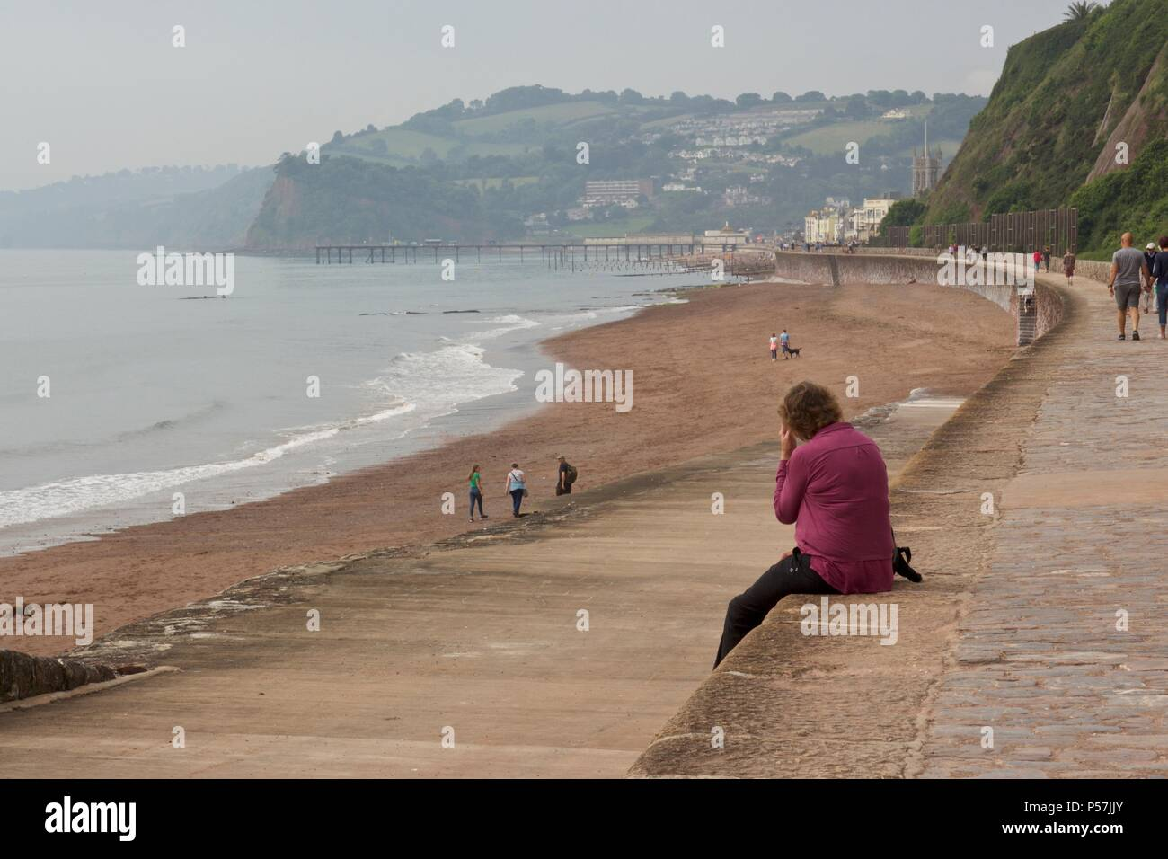 A woman sitting on the edge of the sea wall, looking out onto Teignmouth beach in South Devon - Stock Image
