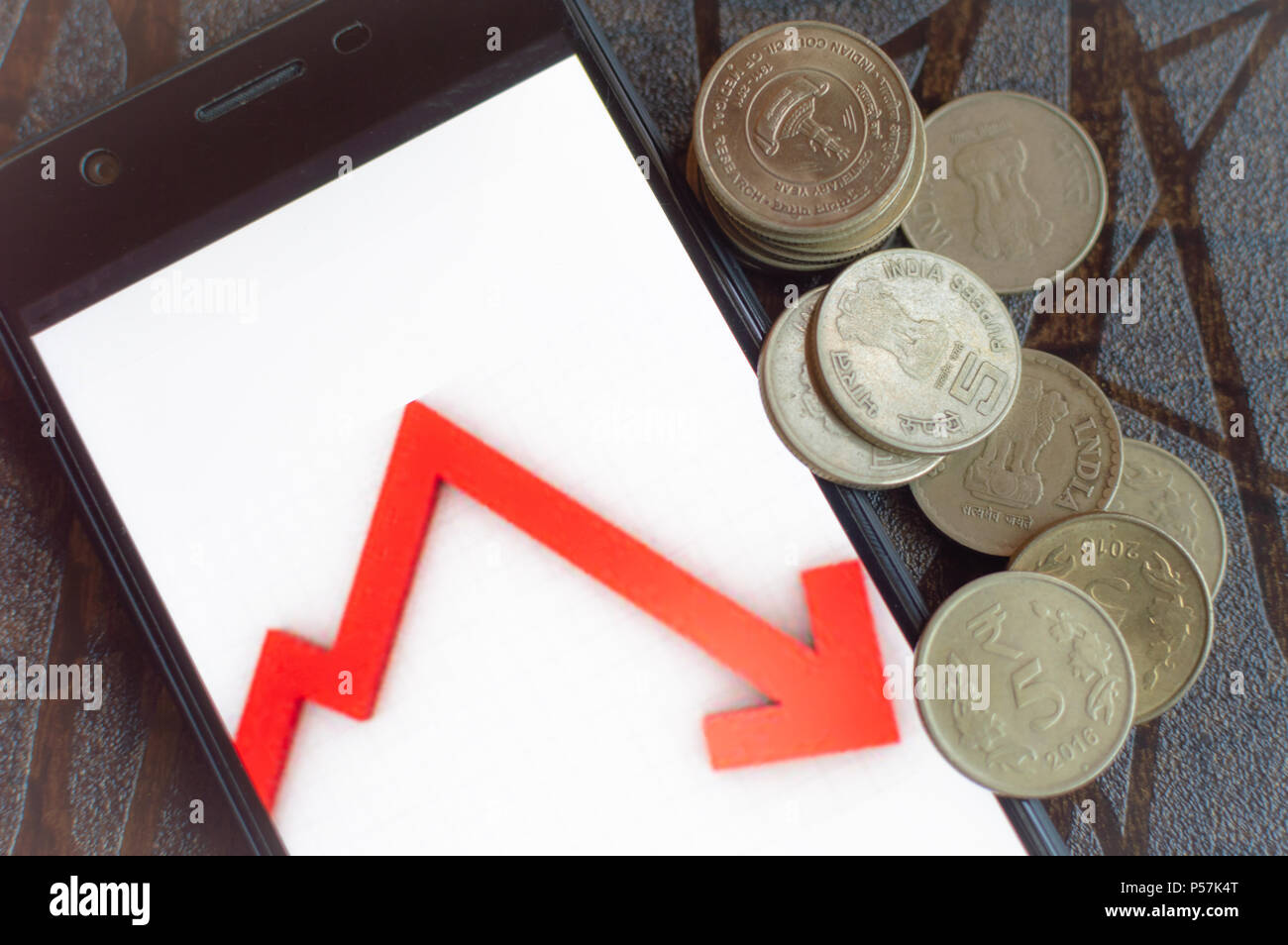 Indian Stock market falls. Mobile app for stock market. Shares sold for coins - Stock Image