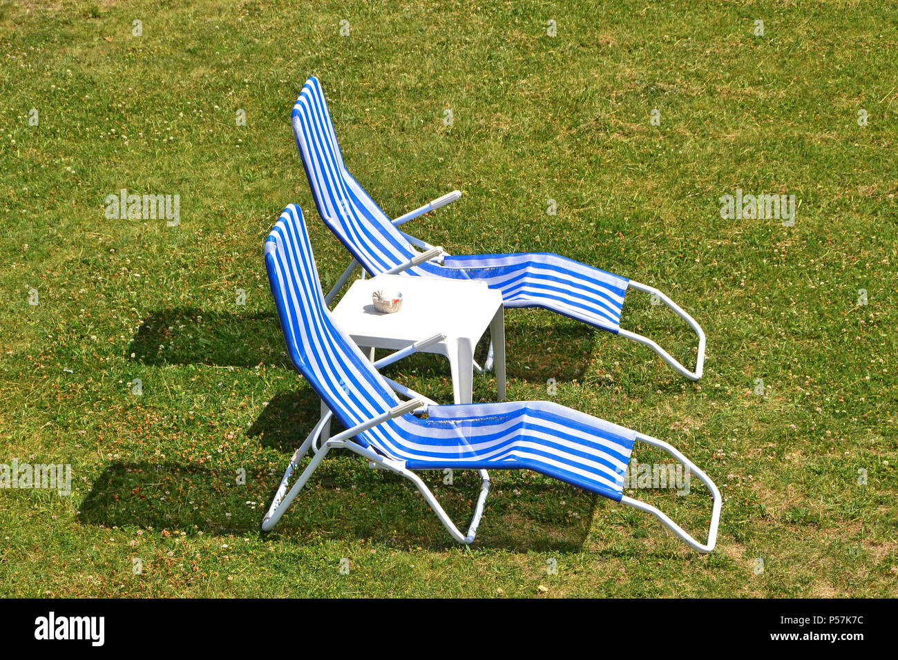 Deckchairs on a meadow in summer - Stock Image