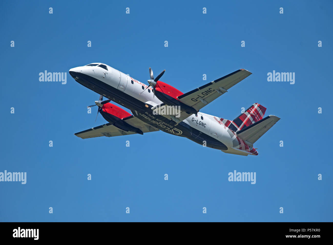 the Loganair Saab 340 in its Scottish Tartan Liver leaving Inverness Airport for its daily flight across to Stornoway in the Outer Hebrides. - Stock Image