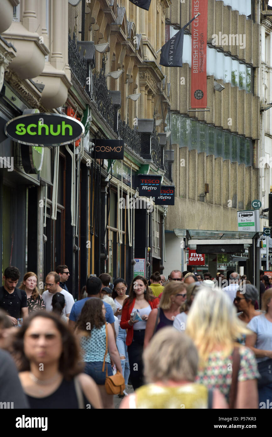 Shoppers and tourists walk along Magdalen Street, Oxford where high street retailers including supermarkets Sainsbury's local, Tesco Metro, the shoe r - Stock Image