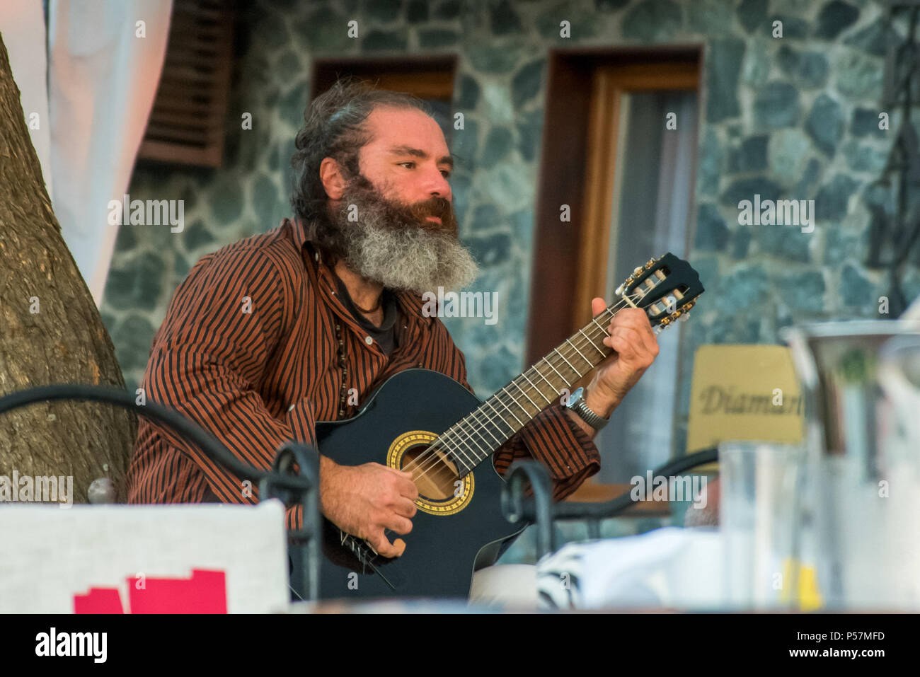 Sozopol, Bulgaria - September 11, 2016: Street musician playing music on an acoustic guitar for the entertainment of tourists in street cafe Stock Photo
