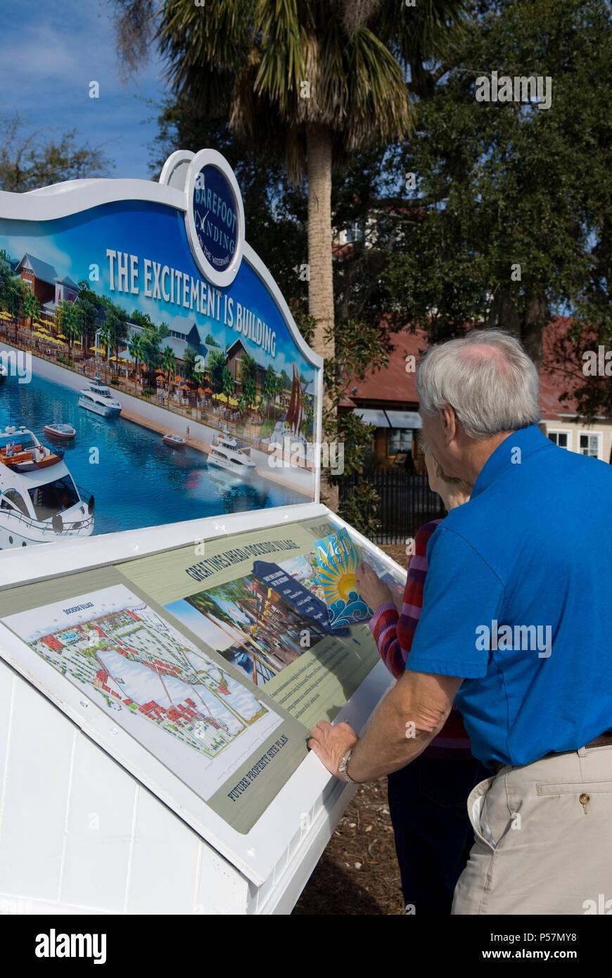 Senior Couple Views Barefoot Landing information board at Myrtle Beach SC USA - Stock Image
