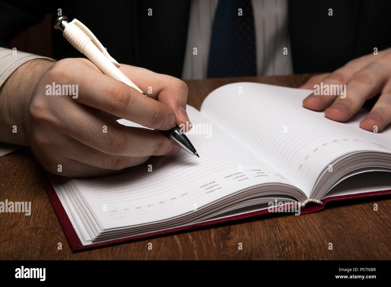 man running with diaries with pen close up - Stock Image