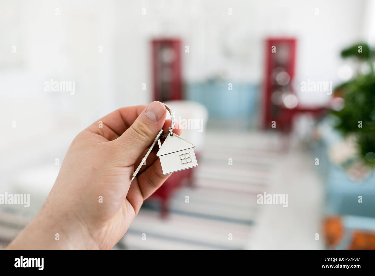 Mortgage concept. Men hand holding key with house keychain. Modern light lobby interior. Real estate, moving home or renting property. - Stock Image
