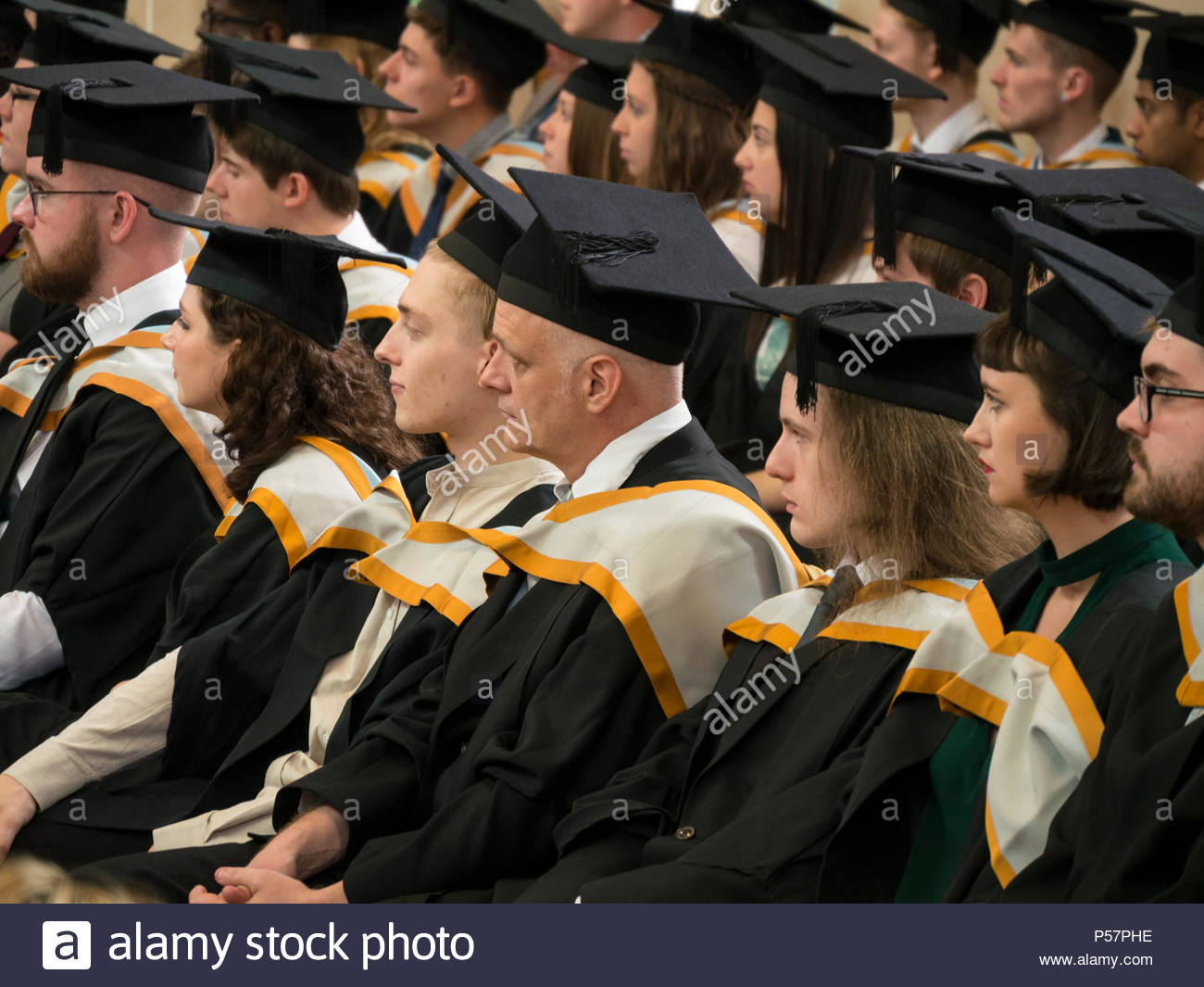 Batchelor of Arts Graduates in mortarboard caps and gowns awaiting their degrees at Graduation Day 2017, Norwich University of the Arts, England, UK - Stock Image