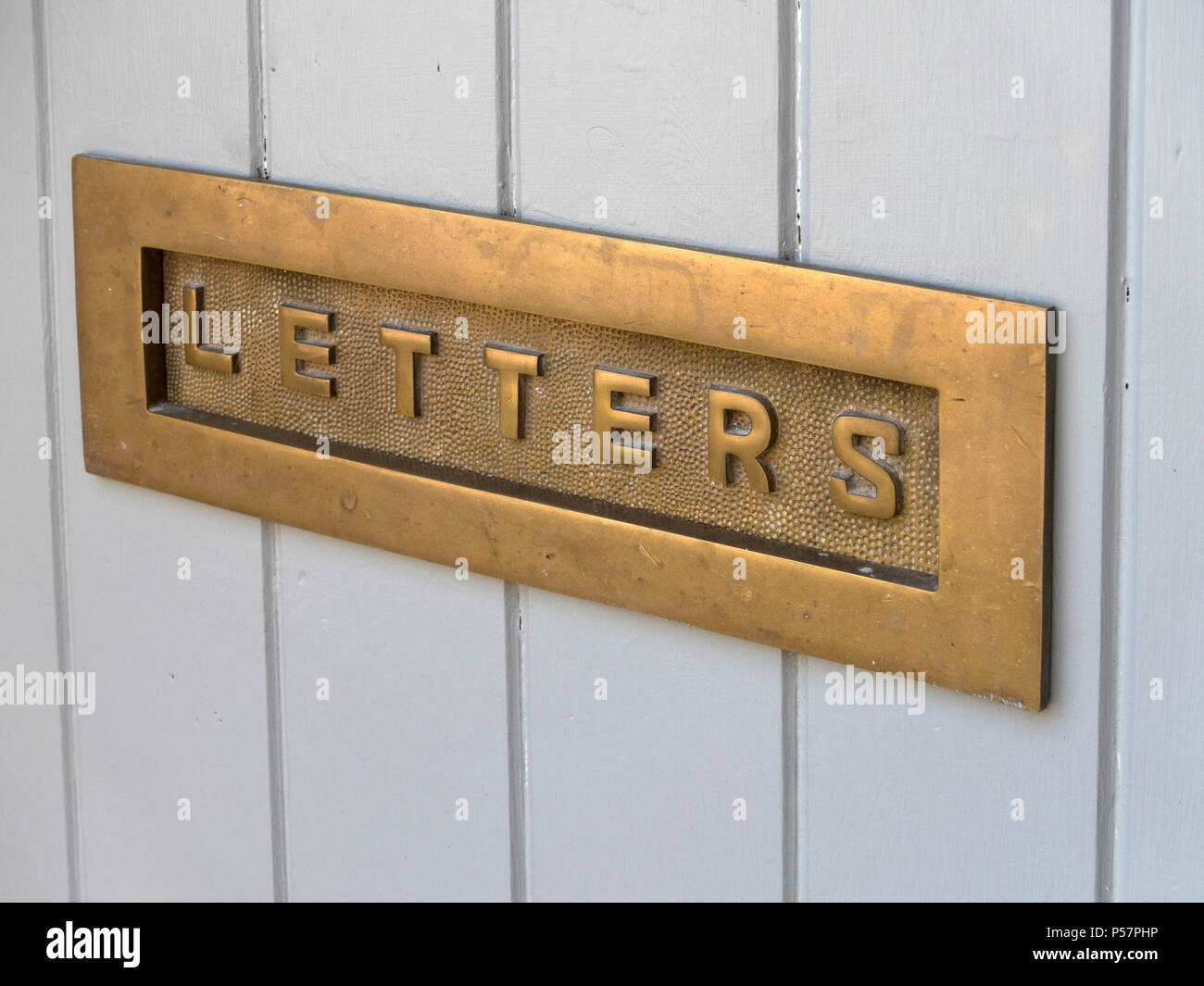 Old decorative cast brass metal house letterbox with the word 'letters' set in wooden door - Stock Image