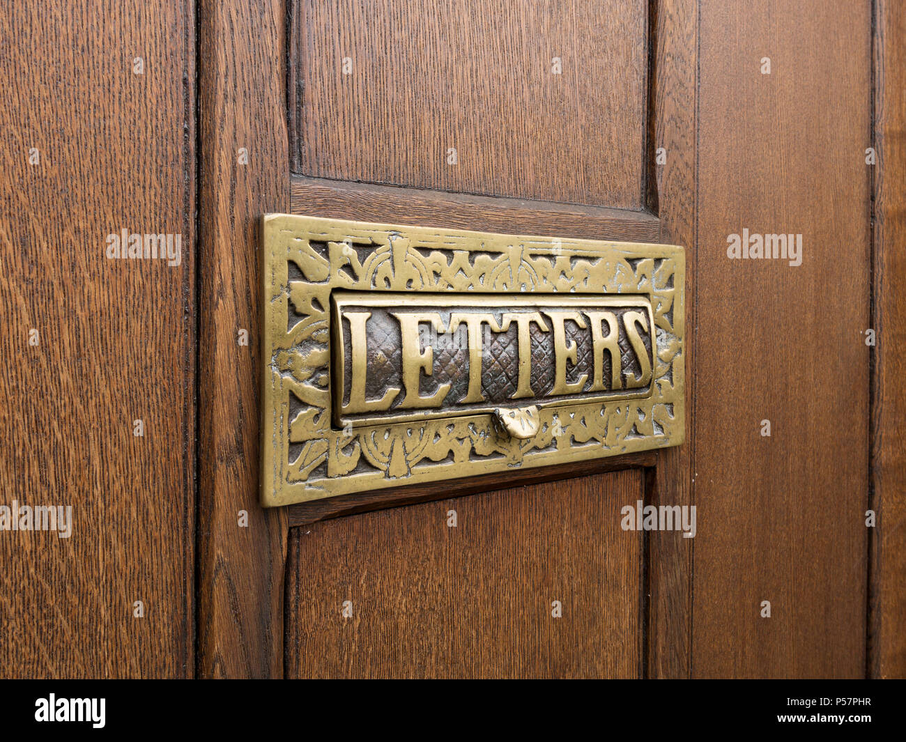 Old ornate decorative cast brass metal house letterbox with the word 'letters' set in wooden door - Stock Image