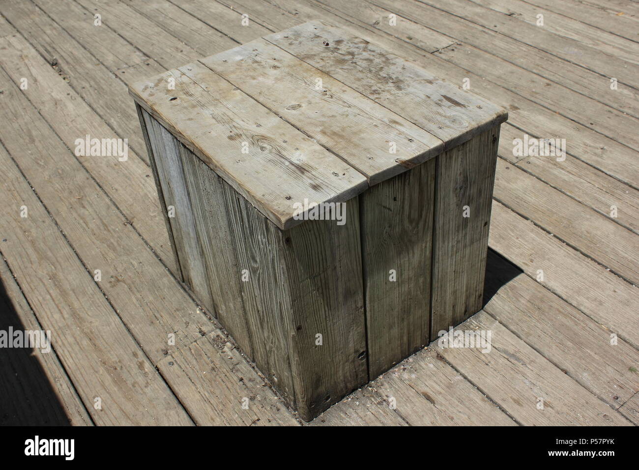 Permanent fishing cube stool found on the fishing deck of the Wildwood Nature Center in suburban Park Ridge, Illinois. - Stock Image