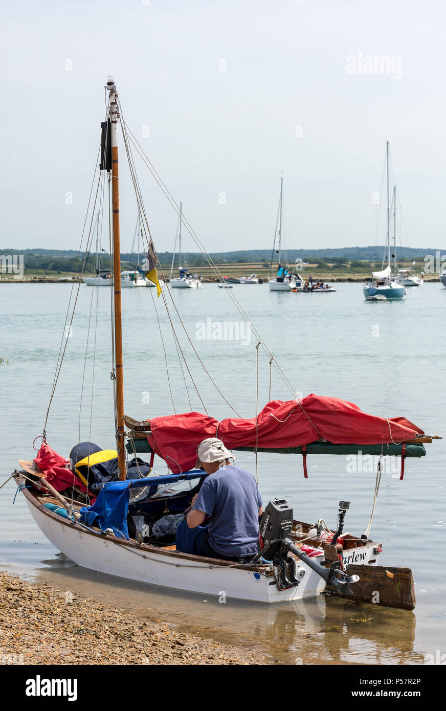 an older man in a sailing dinghy, isle of wight. - Stock Image
