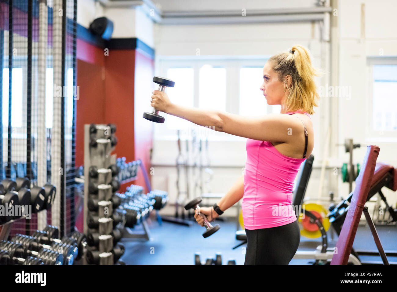 5efefce42cb50 Caucasian blonde Scandinavian fitness girl training at gym. Strong beautiful  european girl workout her body. Nice healthy swedish athletic young woman