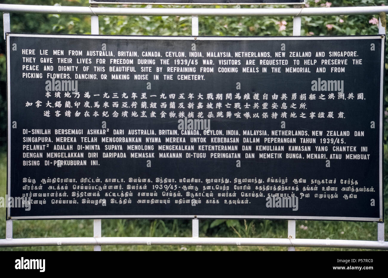 An outdoor sign in four languages unexpectedly requests visitors not to cook meals, pick flowers, dance, or make noise in the Kranji War Memorial, a hillside cemetery in Singapore that honors soldiers from nine nations who gave their lives in the line of duty during World War II. White gravestones mark the remains of 4,461 men and women from Australia, Britain, Canada, Ceylon (now Sri Lanka), India, Malaysia, Netherlands, New Zealand and Singapore. Stock Photo