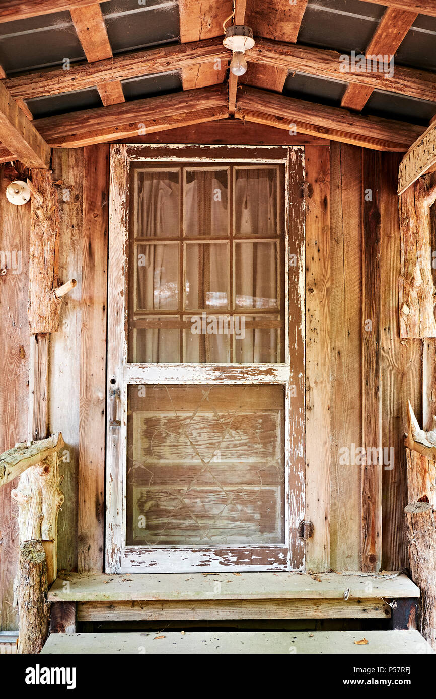 Old antique wooden screen door in a vintage cabin with a covered porch in  rural Alabama, USA. - Old Antique Wooden Screen Door In A Vintage Cabin With A Covered