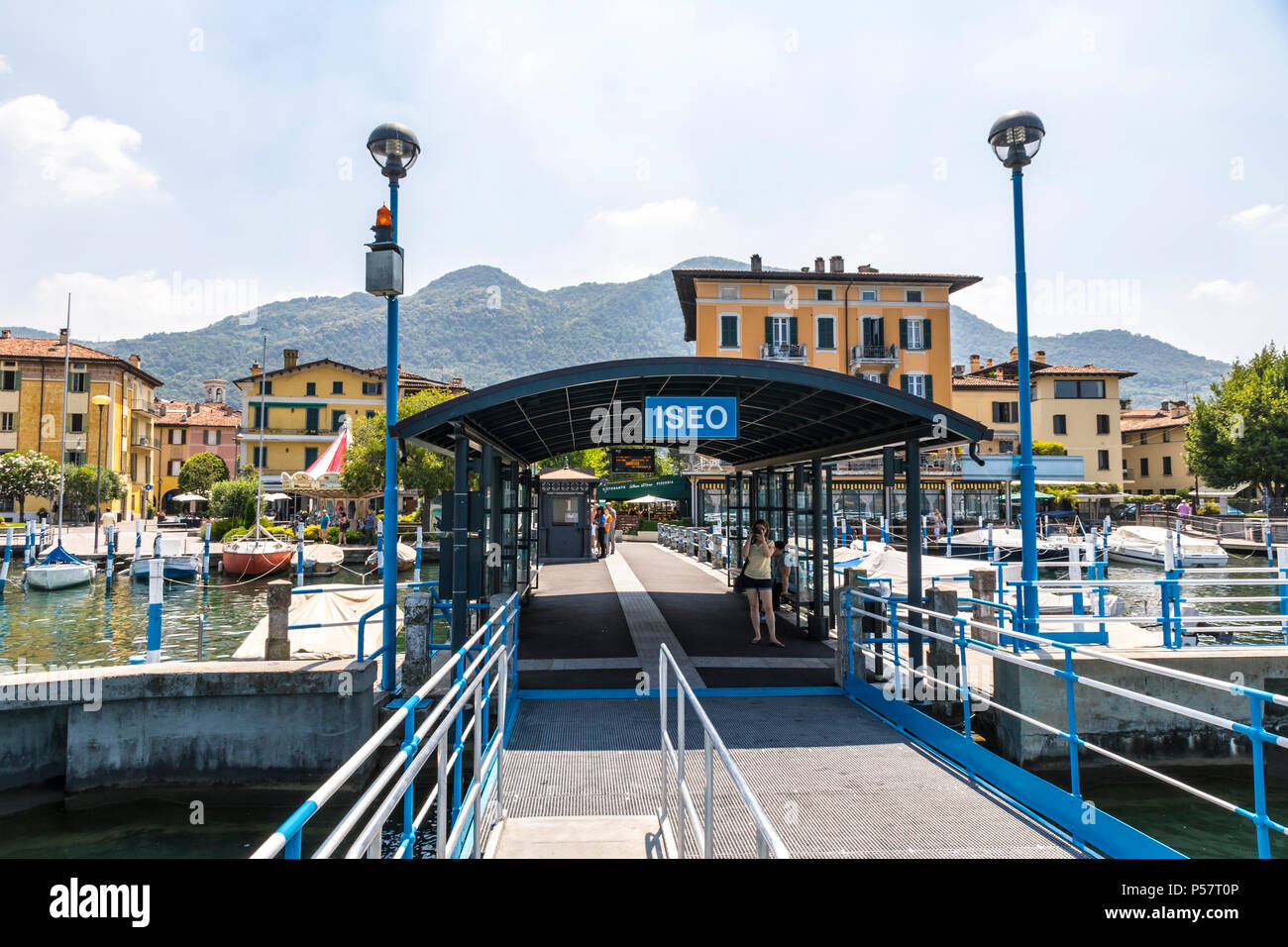Ferry station on Iseo lake (Lago d'Iseo) in Iseo city, Lombardy, Italy. View to the city from the pier. Iseo is a famous Italian resort - Stock Image