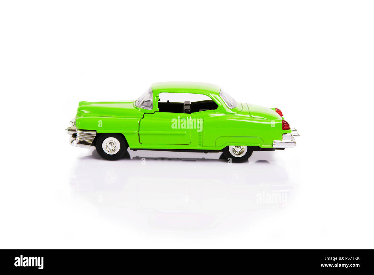 Side view of green model toy car in retro style on white background. - Stock Image