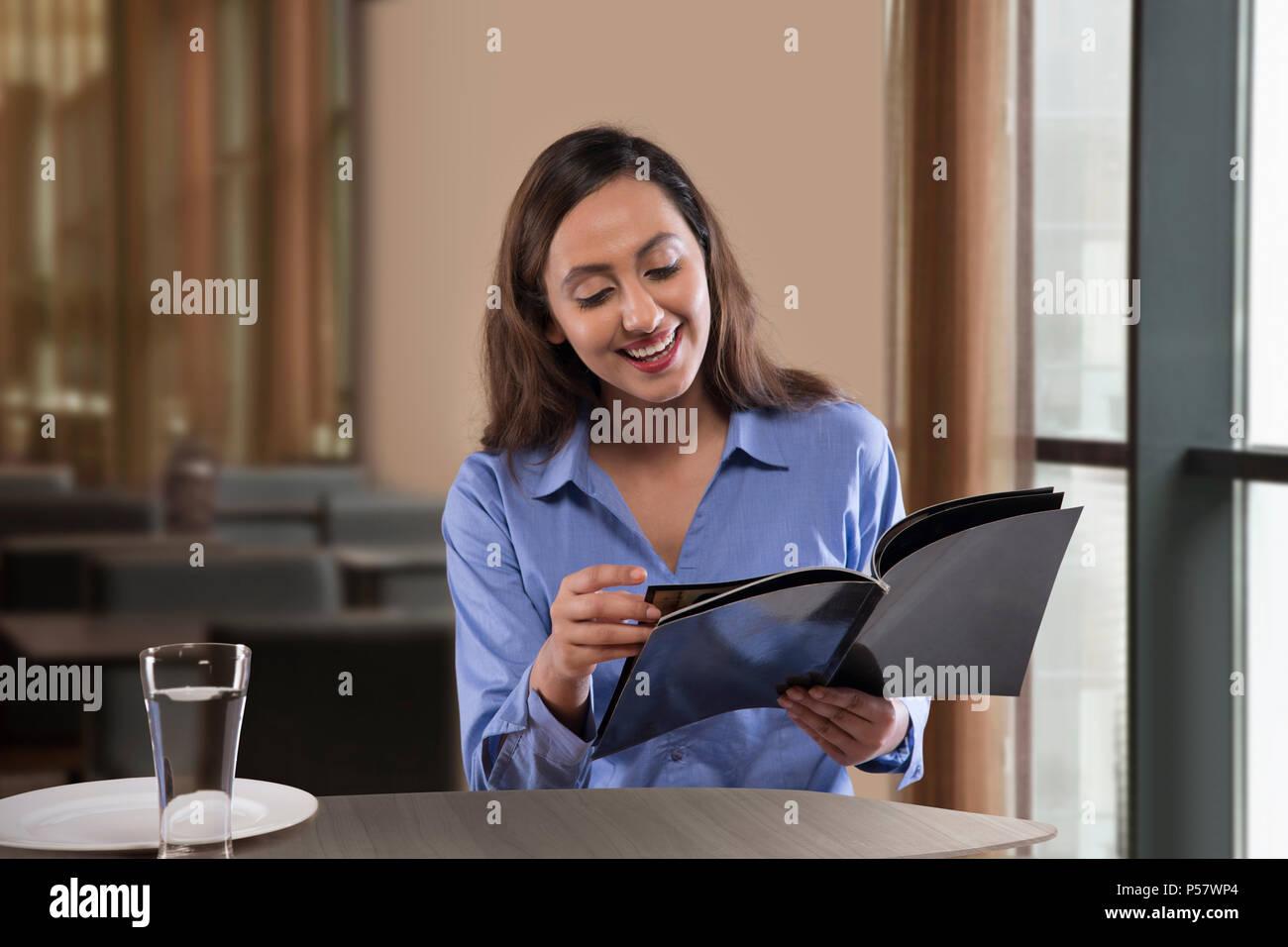 Businesswoman reading magazine on table - Stock Image