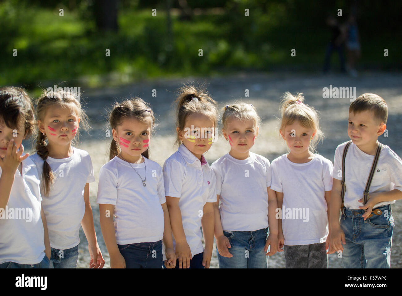 Group of little children in white t-shirts with painted faces lined up in line in summer day - Stock Image