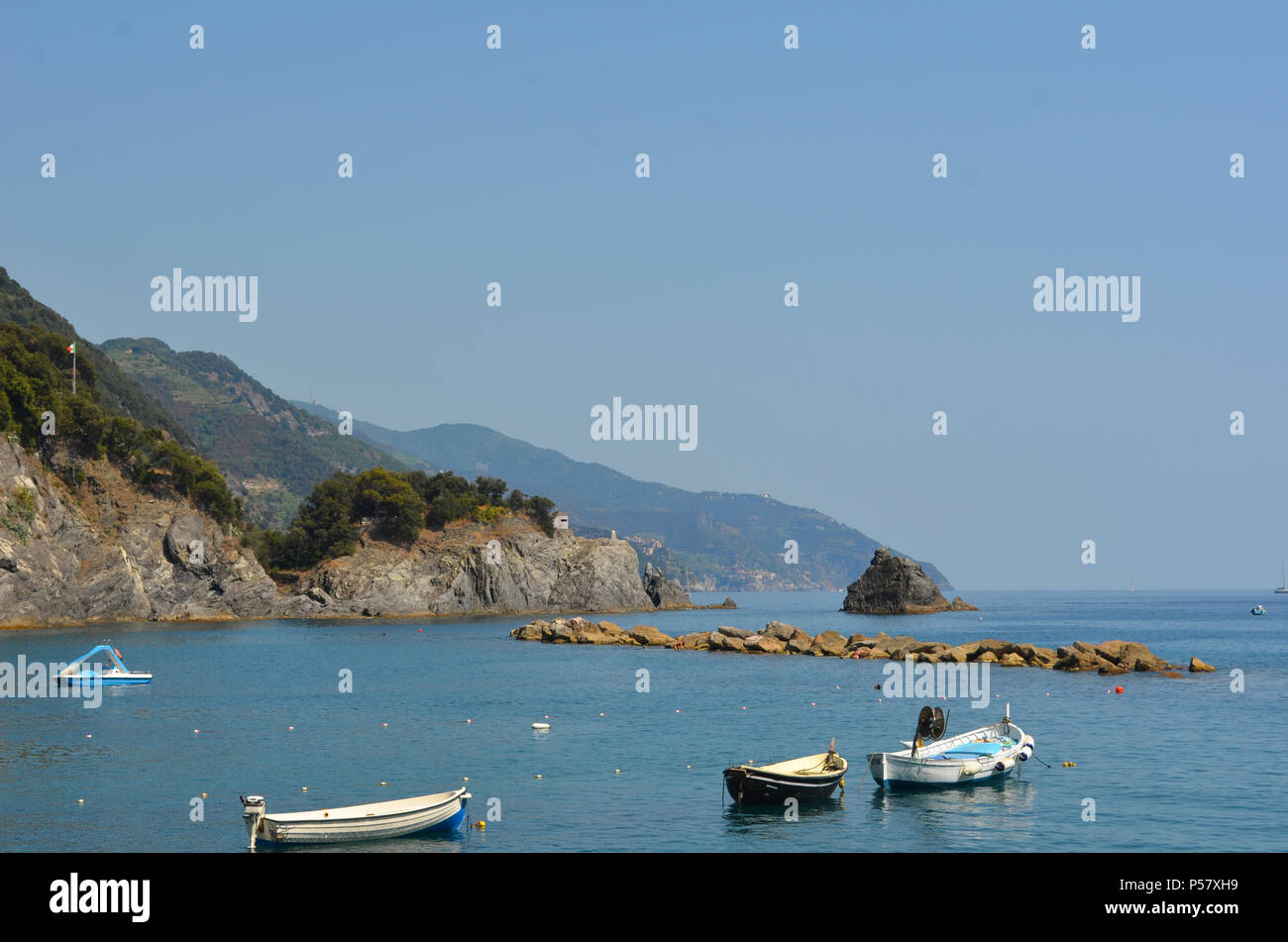 Small boats with outboard motors are moored in a quite bay. A breakwater and a small isalnd are in front of them, and rocky hills to one side. the sky - Stock Image