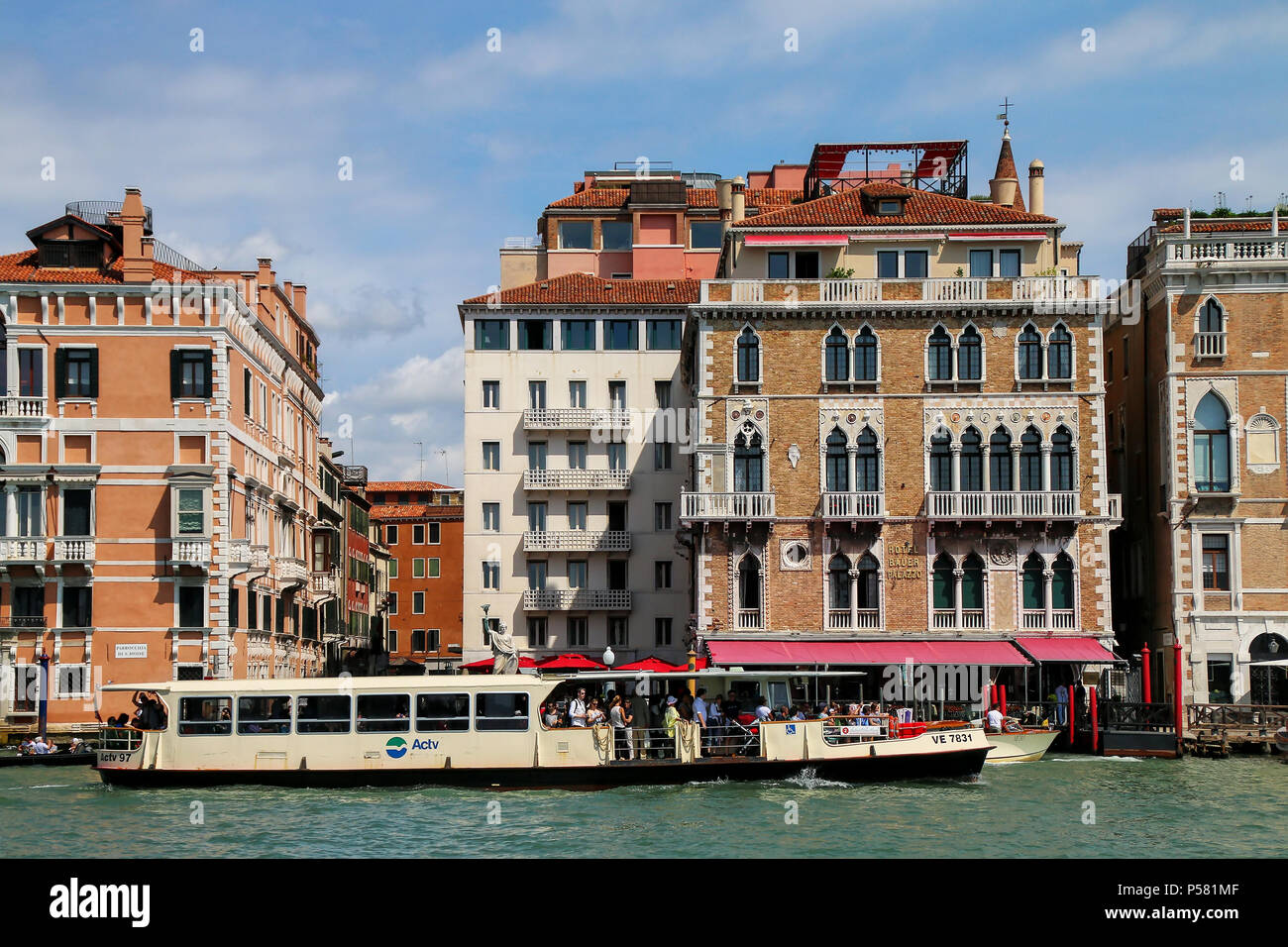 Vaporetto (water public bus) moving on Grand Canal in Venice, Italy. Venice is situated across a group of 117 small islands that are separated by cana - Stock Image
