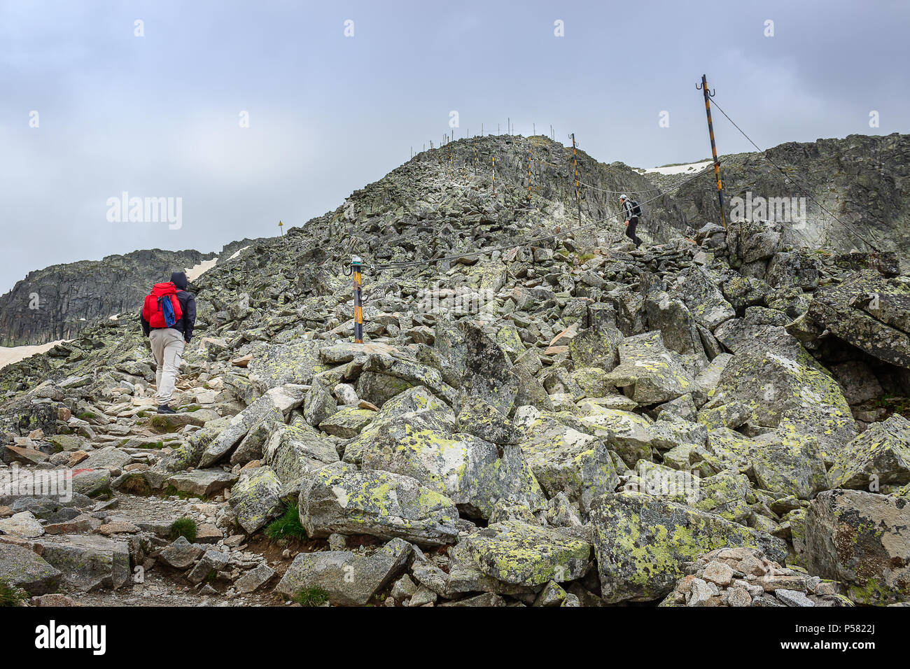 Mountain hikers climbing up the final, rocky reef in front of Musala summit on Rila mountain in Bulgaria - Stock Image