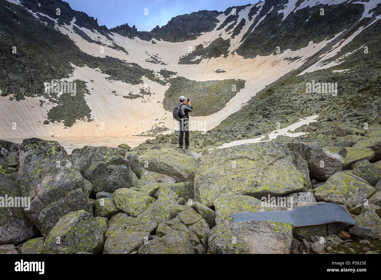Hiker with backpack taking photo with his mobile phone of Frozen lake and snowy landscape on Rila mountain on the track to Musala hilltop - Stock Image