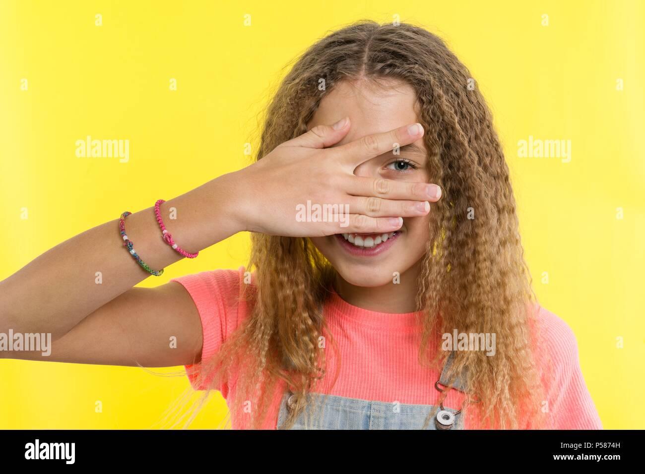 Portrait of teenage girl peeps through fingers. Yellow studio background. - Stock Image