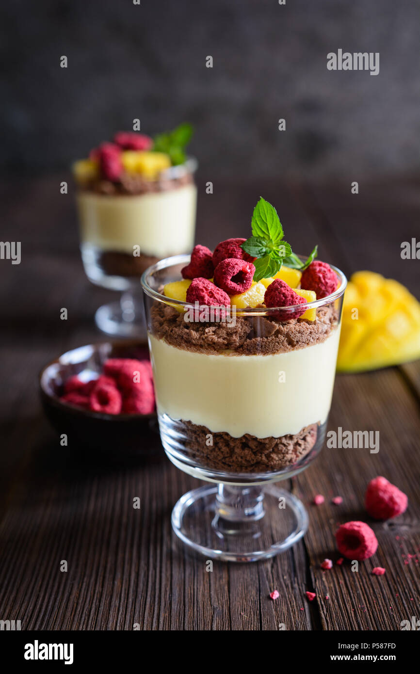 Layered mango dessert with cream cheese, crushed biscuits and freeze dried raspberries served in glass jars Stock Photo