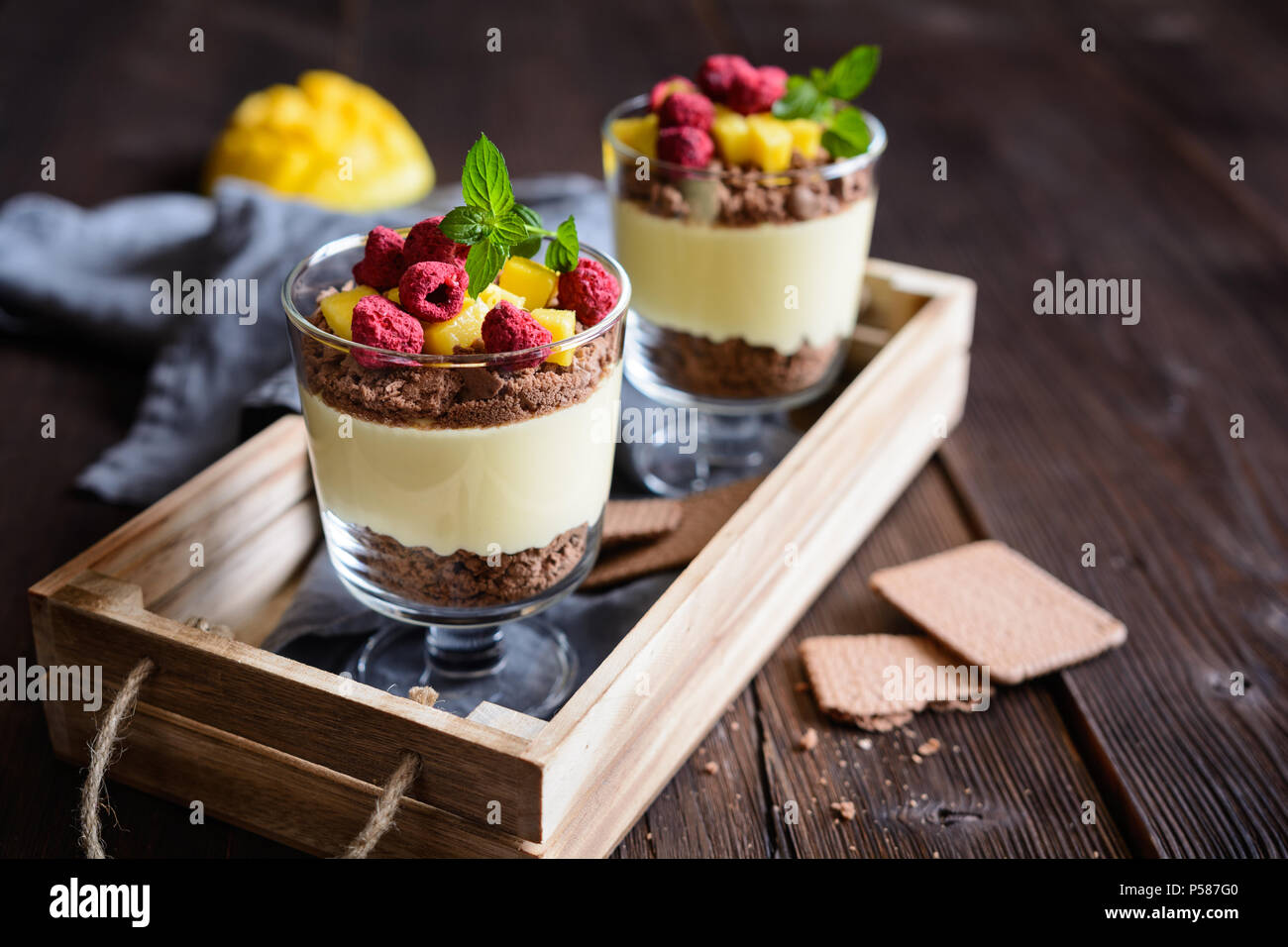 Layered mango dessert with cream cheese, crushed biscuits and freeze dried raspberries served in glass jars - Stock Image