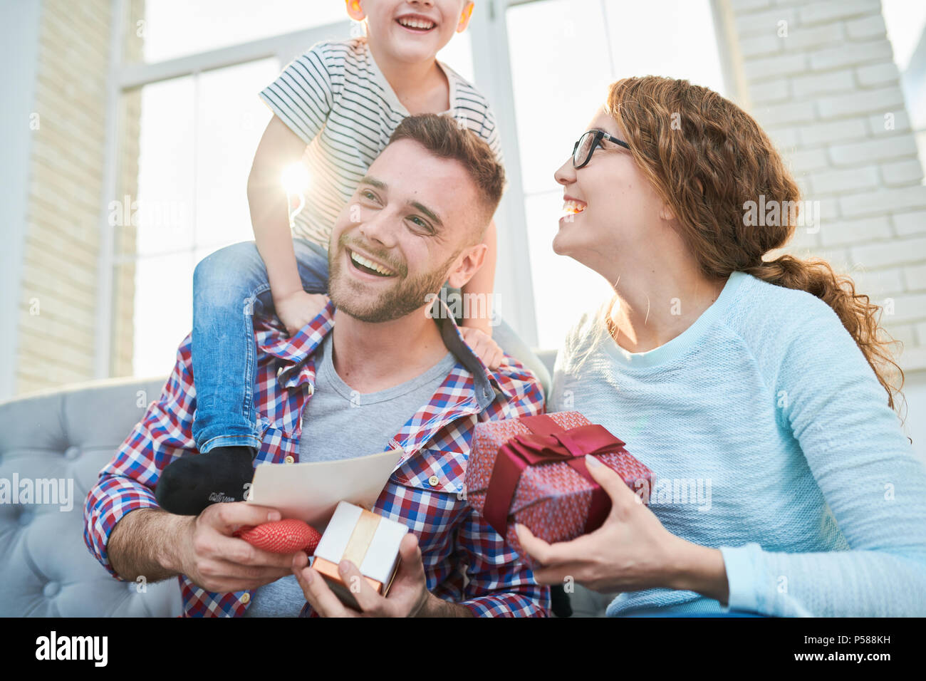 Warm toned portrait of playful happy family holding presents siting on sofa in living room at home, focus on smiling handsome man - Stock Image