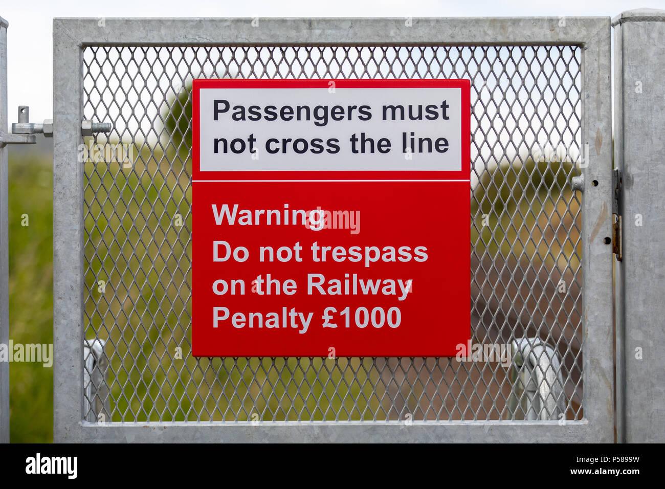 Passengers must not cross the line railway warning sign - Stock Image