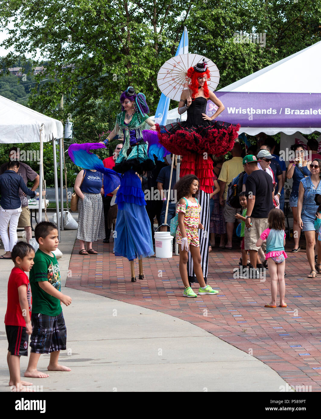 Two women on stilts overlook festival goers at Hola Carolina Asheville in NC, USA - Stock Image