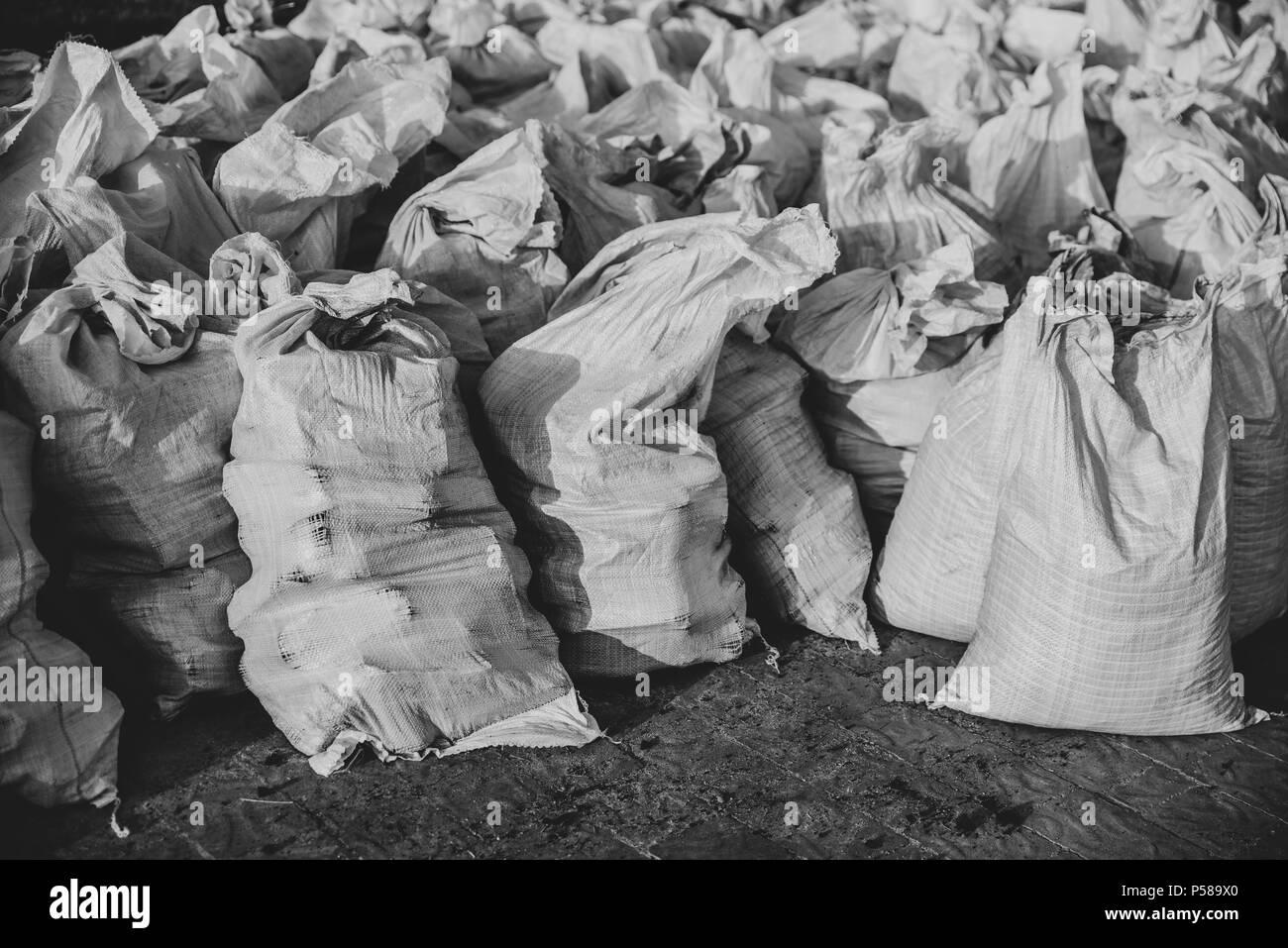 Group of filled plastic woven sacks, polypropylene bags - Stock Image