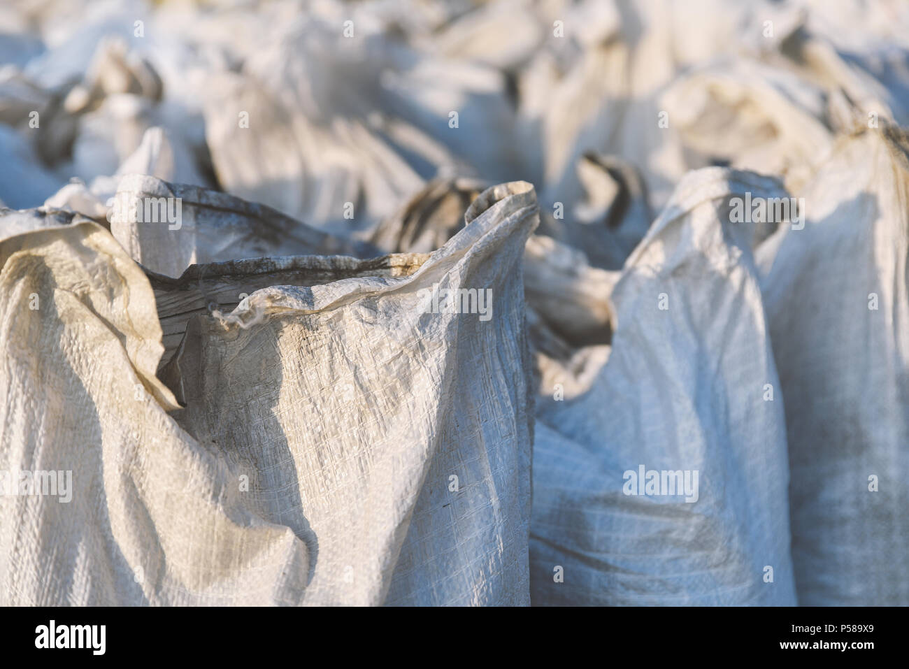 Group of filled plastic woven sacks, packing of goods for transportation and storage in a warehouse, polypropylene bags closeup - Stock Image