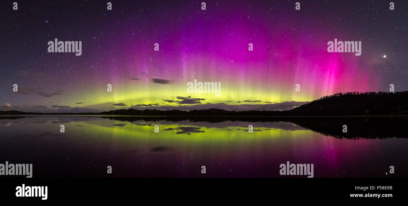 Bright and colourful aurora display with reflections - Stock Image
