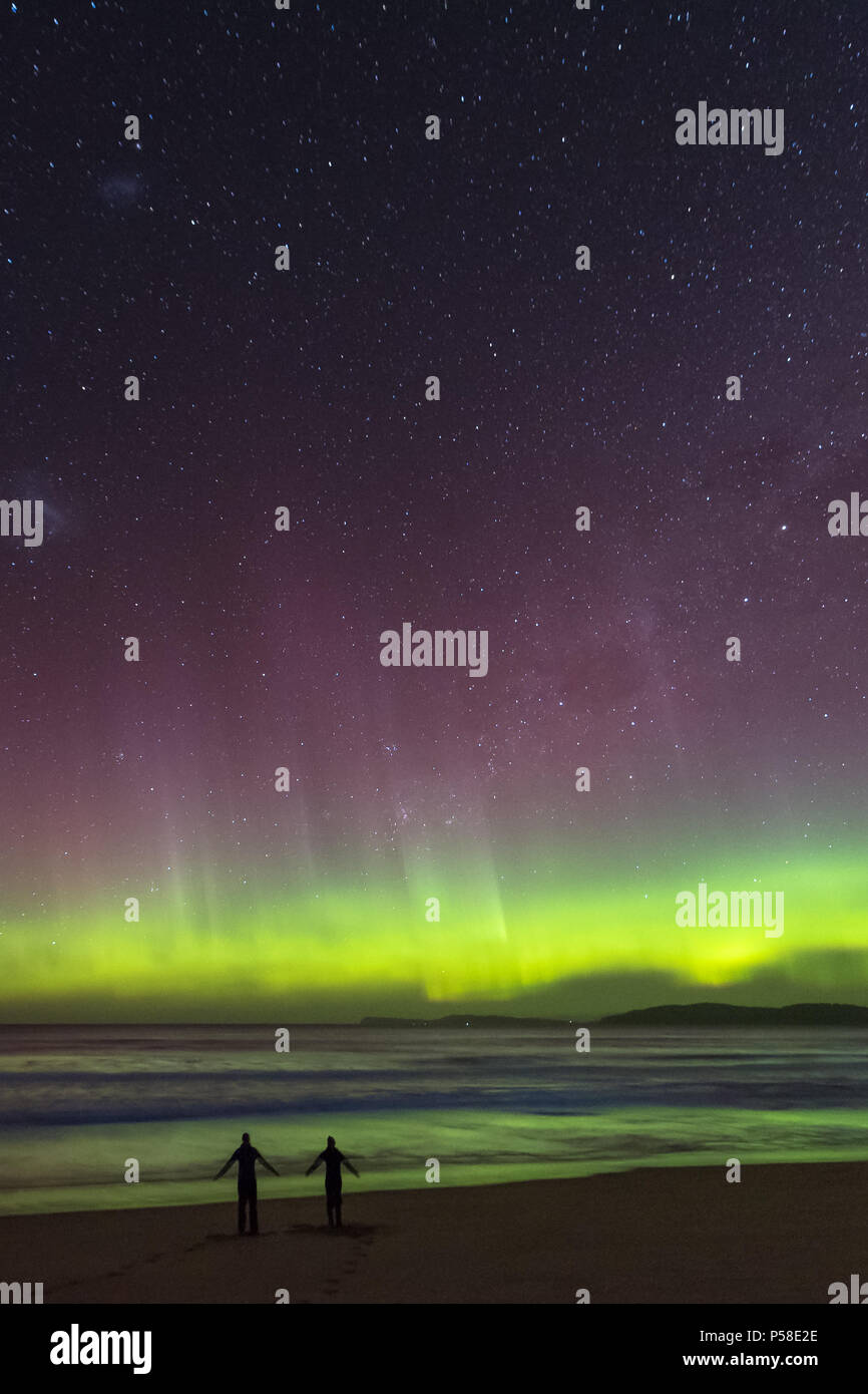 Couple on the beach under the Southern Lights Aurora - Stock Image