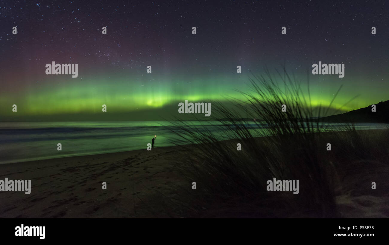 Figure on beach with aurora dancing overhead - Stock Image