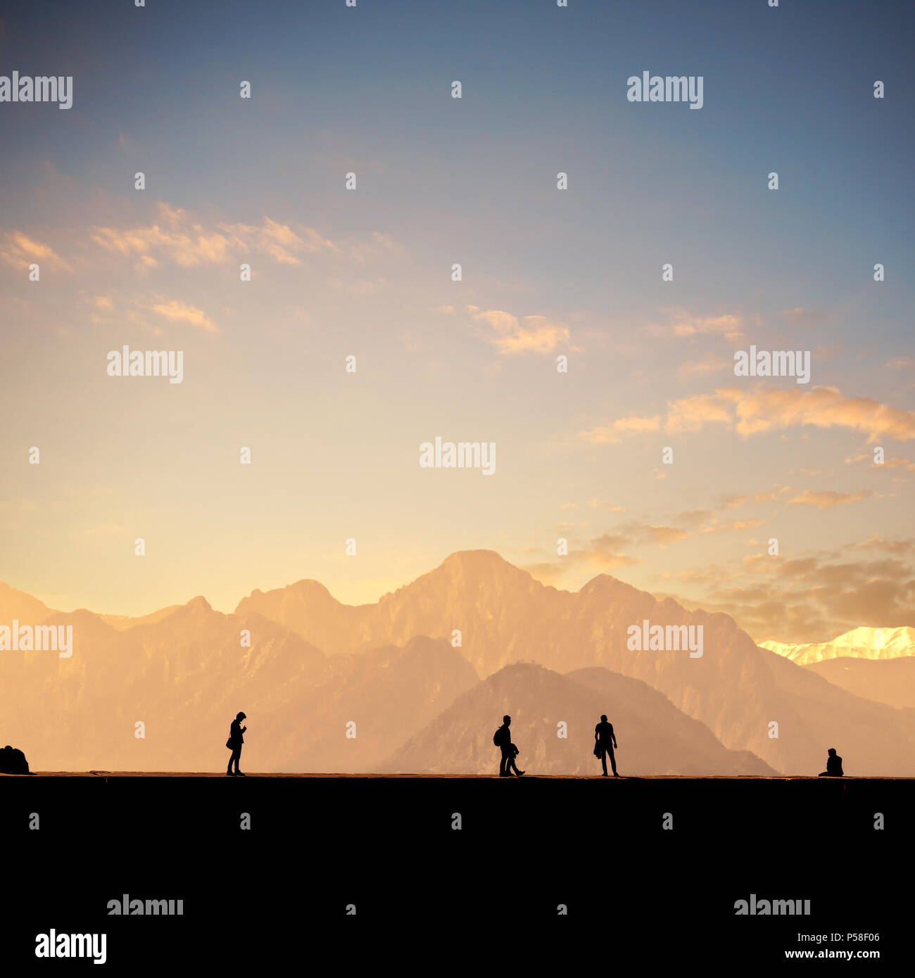 Silhouetted people relaxing in Antalya harbor over sunset sky and high mountains - Stock Image