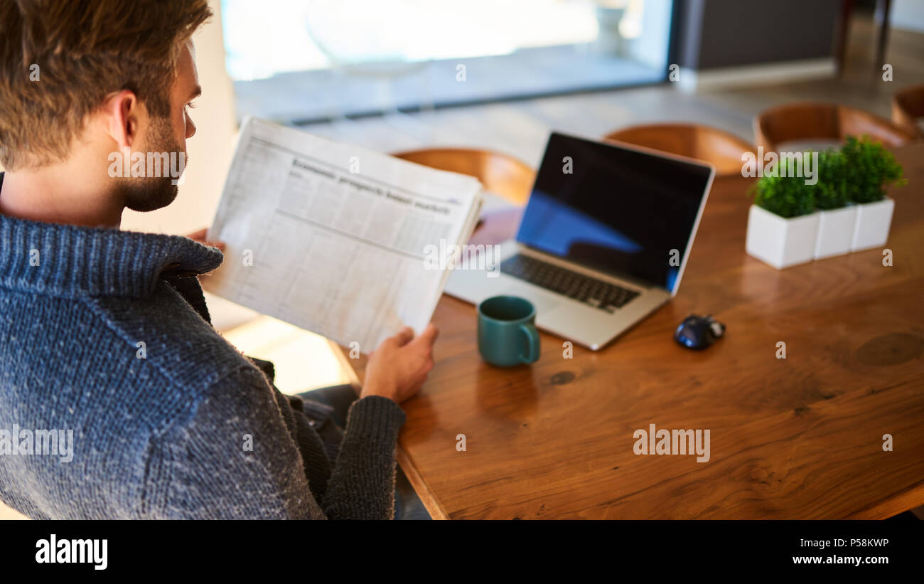 over the shoulder image of an attractive young man holding a newspaper while seated at his beautiful wooden dining table at home, with a hot cup of tea and his laptop ready to work. Stock Photo