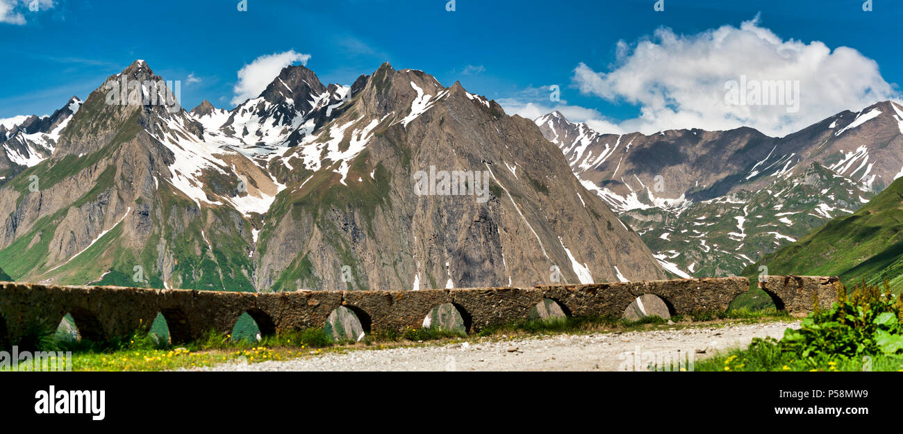 landscape of mountains of Formazza Valley in a clear day of spring with wall in the foreground with blur and blue sky and clouds in background, Italy - Stock Image