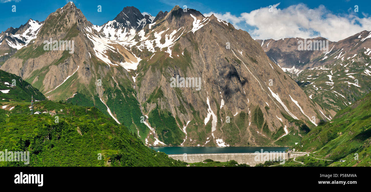 Mountains and Lake of Morasco in stunning panorama with dam in foreground, spring season - Stock Image
