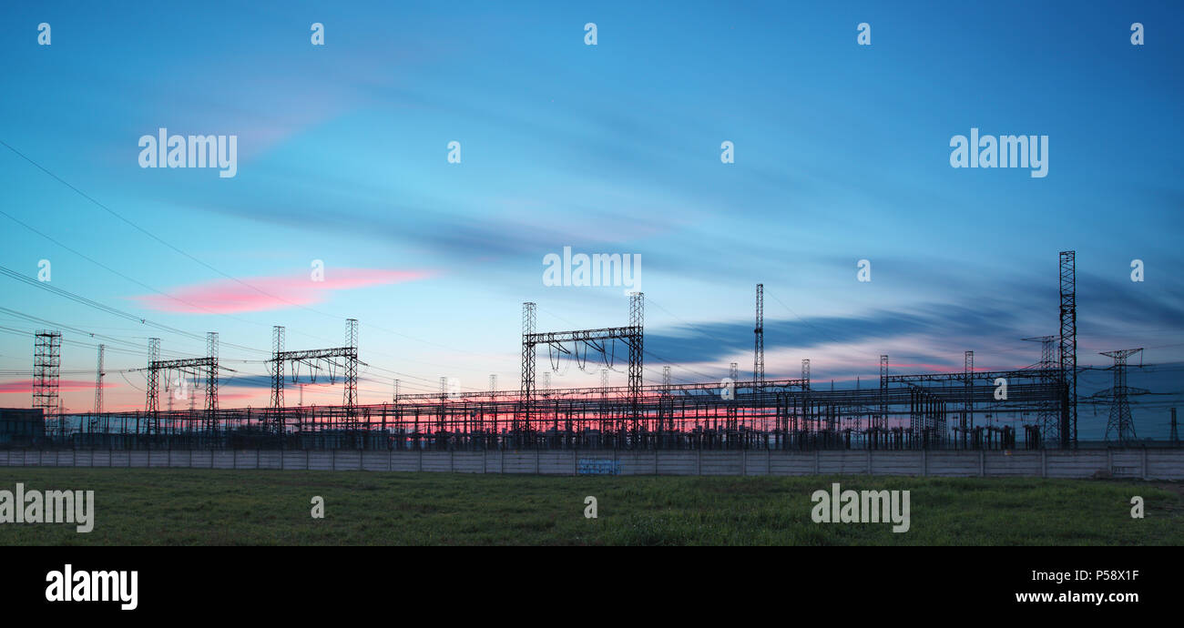electricity transmission pylon silhouetted against blue sky at dusk - Stock Image