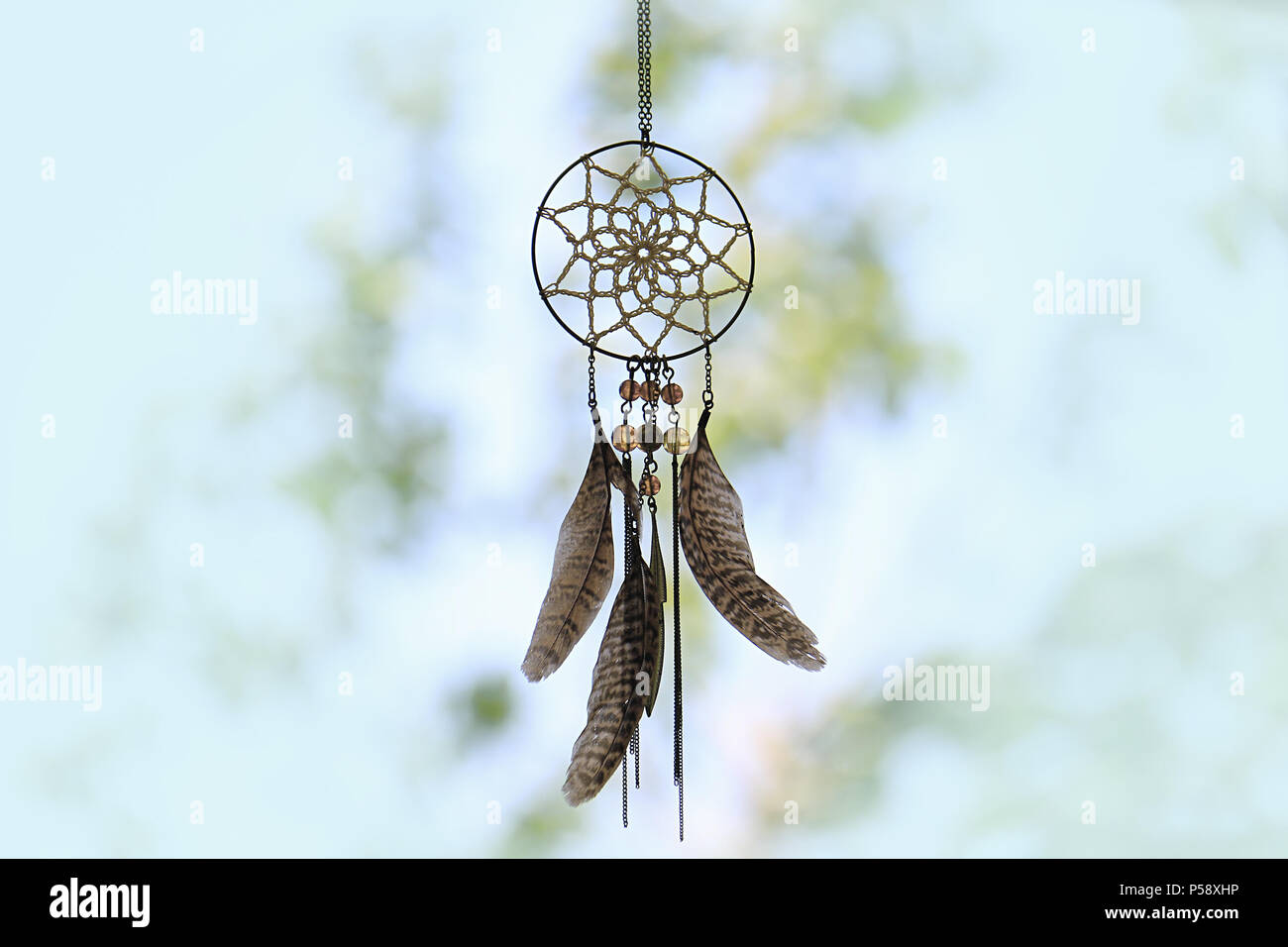 A dreamcatcher against a blurred background of leaves. - Stock Image