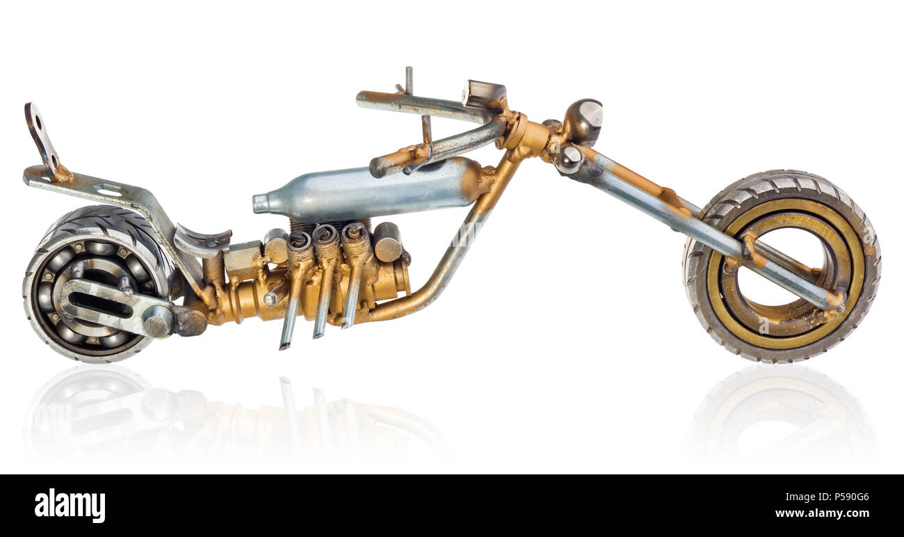Handmade miniature of a chopper motorcycle. Decorative vehicle made of mechanical parts, bearings, wires, car candles, screws, plates. Toy in silver-g - Stock Image