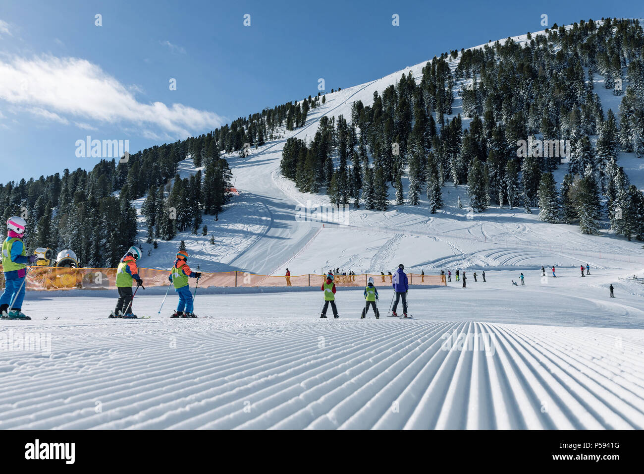 A group of skiers in the background on a modified slopes in the Dolomites on a sunny day. Prepare ski slope. Val di Fiemme - Stock Image