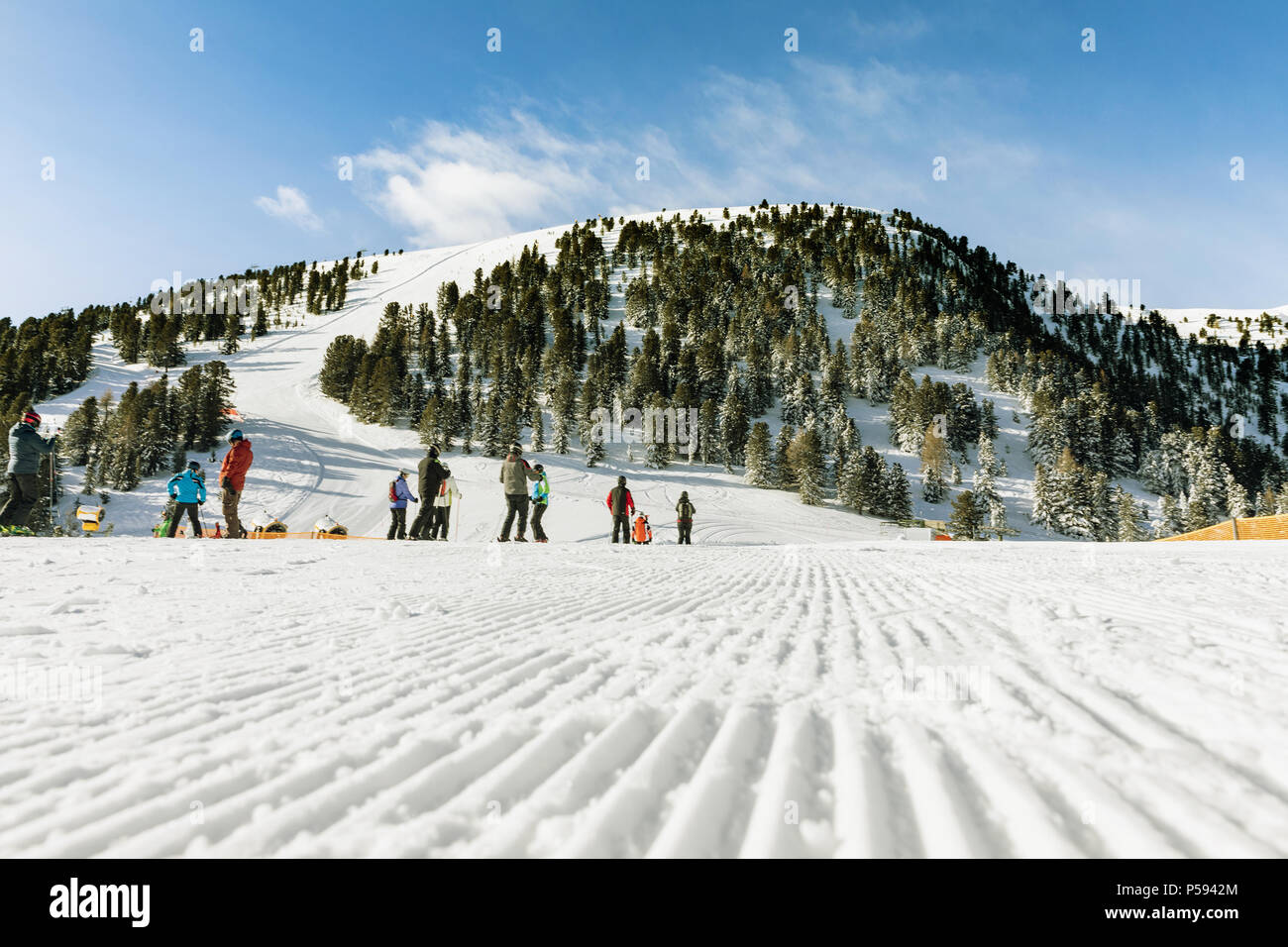 A group of skiers in the background on a modified slopes in the Dolomites on a sunny day.. Empty ski slope in winter on a sunny day. Prepare ski slope - Stock Image