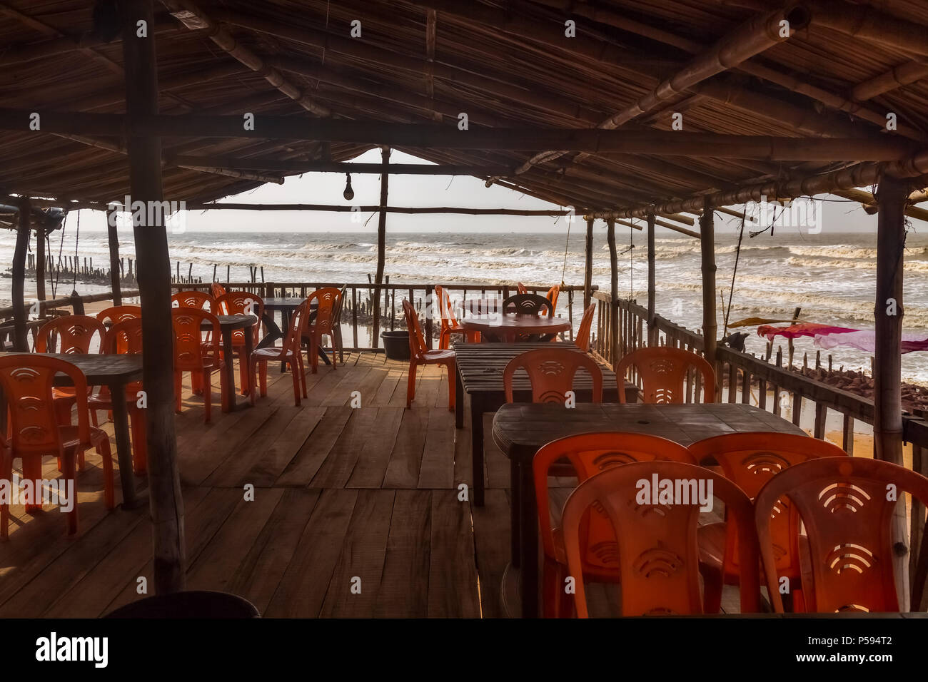 Interior view of a local beach restaurant with plastic chairs thatched roof and wooden floor with view of the sea beach at Talsari West Bengal, India. - Stock Image