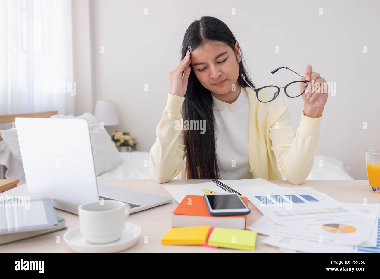 Asian female freelancer headache and stress while working with laptop on table in bedroom at home.Work at home concept.work from home concept - Stock Image